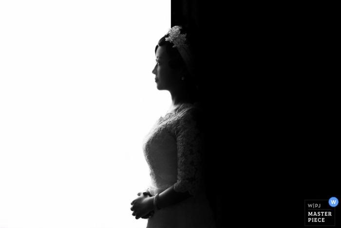 Das Profil der Braut wird in der Mitte durch Schatten und Licht in diesem Schwarzweißfoto von einem Hochzeitsfotografen aus Jiangxi, China geteilt.