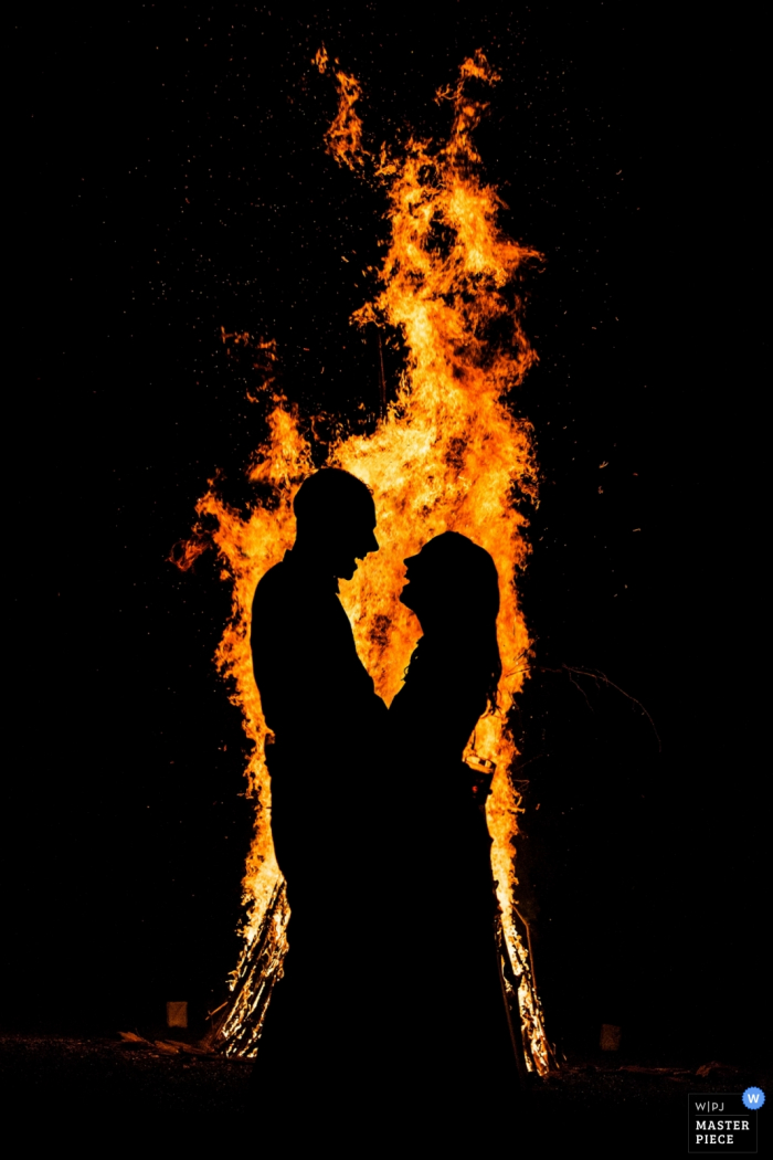 The bride and groom stand in front of a large bonfire at night in this photo by a New Jersey wedding photographer.