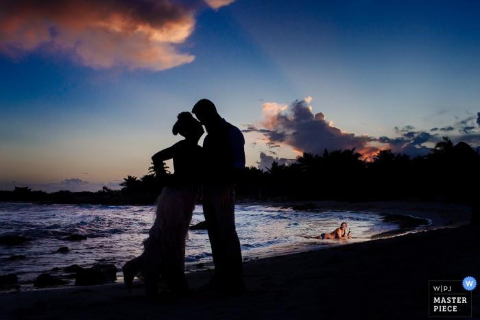 Die Braut und der Bräutigam werden auf einem Strand silhouettiert, während sie in diesem Foto durch ein Playa del Carmen küssen.