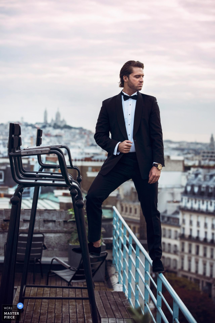 Paris, France wedding day portrait of the groom standing on a chair and a roof top guard rail as he looks into the distance