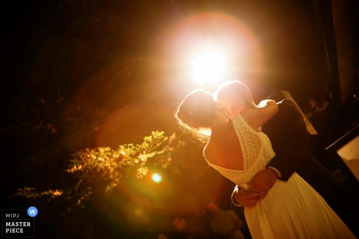 Foto van de bruid en bruidegom knuffelen met lens flare achter hen. Genomen door een huwelijksfotograaf uit Thessaloniki, Griekenland.