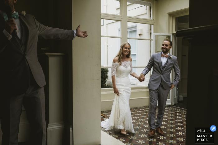 Ein Mann streckt der Braut und dem Bräutigam die Hand entgegen, als sie den Empfang auf diesem Foto eines Hochzeitsreportagefotografen aus North Yorkshire, England betreten.