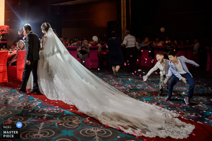 Photo of two young boys throwing flower petals as the bride's long train passes by a Taipei, Taiwan wedding photographer.