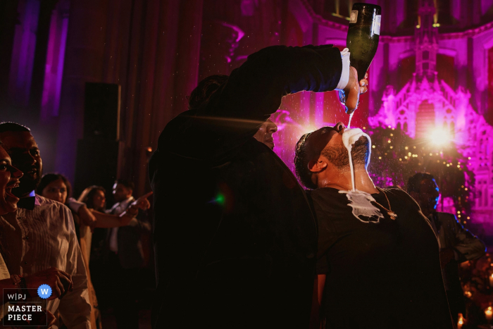 A man pours a bottle of champagne into another man's mouth during the reception in this photo by a London, England wedding reportage photographer.