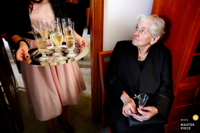 A woman looks up at a server carrying a tray of champagne in this photo by a Calabria wedding photographer.