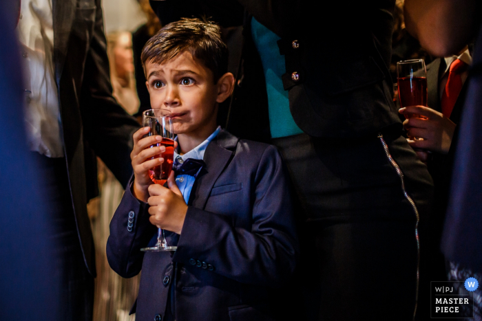A young boy is about to sip from a champagne glass in this photo by a Overijssel, Netherlands wedding photographer.