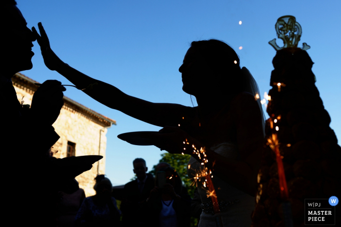The silhouette of the bride smearing cake on the groom's nose as he goes to feed her is visible in this photo by a Lot-et-Garonne wedding photographer.