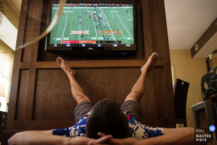 Photo of a many laying on the ground with his feet up as he watches football by a Omaha, NE wedding photographer.
