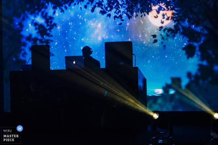 Photo of the DJ silhouetted on an outdoor stage by a Dubai, United Arab Emirates wedding photographer.