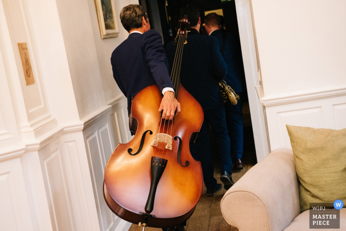 Photo of a man carrying a bass down a hallway by a Scotland wedding reportage photographer.
