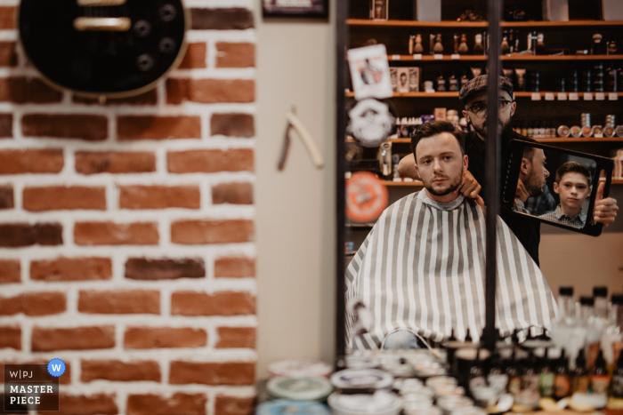 Un barbero sostiene un espejo para el novio en esta foto tomada desde afuera por un fotógrafo de bodas del Centro-Val de Loire.