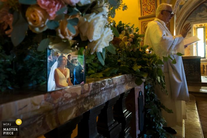 Foto van de bruid en bruidegom weerspiegeld op een mantel als de priester spreekt door een Toscane huwelijksfotograaf.