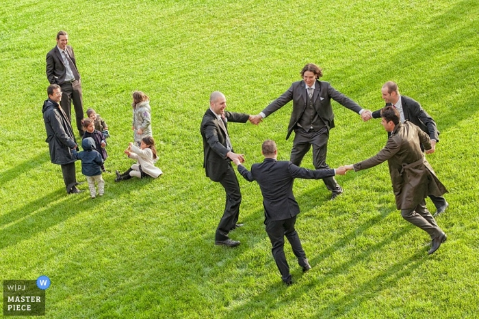 Perugia Umbria Documentary Wedding Photographer | Image contains: guests groomsmen playing grass reception dancing kids