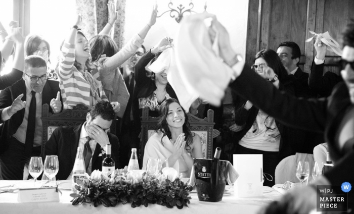 Cosenza wedding photographer captured this black and white photo of the wedding guests toasting the bride and groom