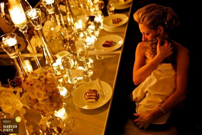 Le photographe de mariage de Chicago a capturé cette photo d'un invité au mariage embrassant son jeune fils pendant le gâteau alors qu'ils sont assis à une table élégamment vêtue