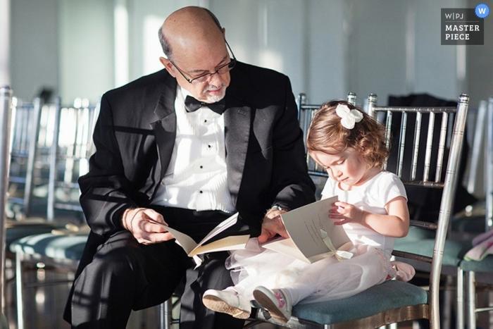 Un photographe de mariage de la Californie du Nord a capturé cette photo de la fille aux fleurs et de son grand-père en train de regarder la brochure sur le mariage