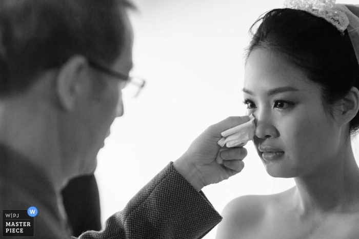 La photographe de mariage de Taipei a capturé cette tendre photo en noir et blanc du père de la mariée épongeant une joue de sa joue avant la cérémonie