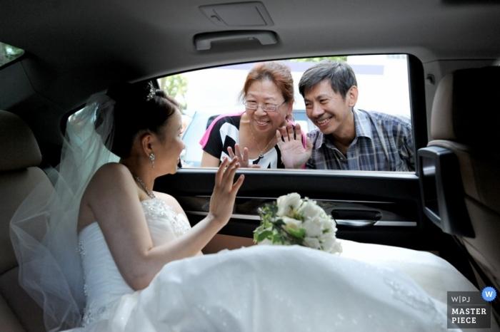 La photographe de mariage de Singapour a capturé cette photo de la mariée en train de dire au revoir à ses parents depuis la fenêtre de la voiture