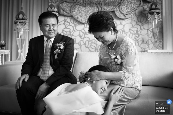 La photographe de mariage de Bangkok a capturé cette photo en noir et blanc de la mariée agenouillée devant ses parents avant la cérémonie de son mariage