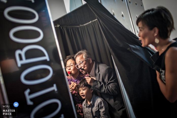 Le photojournalisme de mariage à Singapour - photo d'invités en train de profiter d'un photomaton à la réception