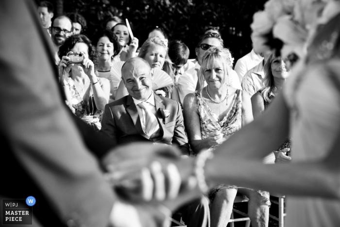 Le photographe de mariage de Phuket a capturé cette photo en noir et blanc des invités du mariage à l'arrière-plan, tandis que les mains jointes des mariés étaient floues au premier plan