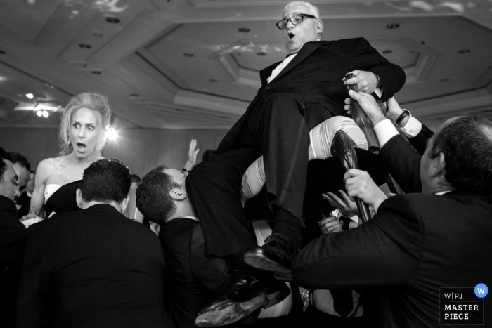 Le photographe de mariage de San Diego a capturé cette photo en noir et blanc de la mariée et du marié qui se font hisser sur des chaises au-dessus de la piste de danse