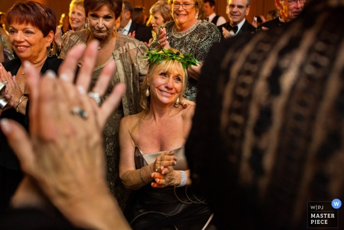 Photographie de mariage à San Diego d'une invitée au mariage pleurant alors qu'elle porte une couronne de feuillage