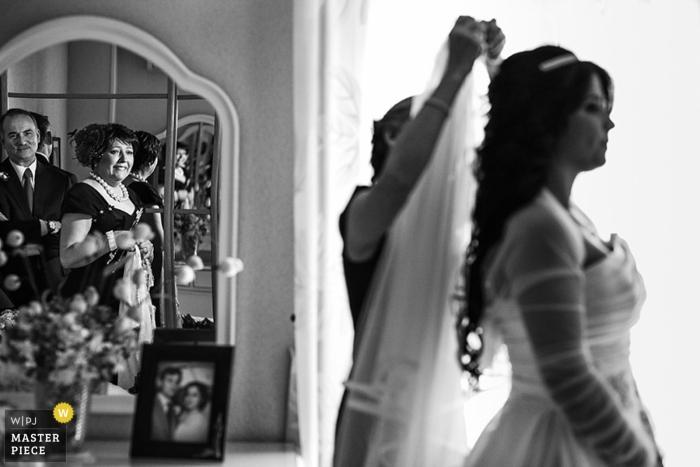 Photographie de mariage à Madrid montrant la mariée portant son voile alors que ses parents regardent à proximité