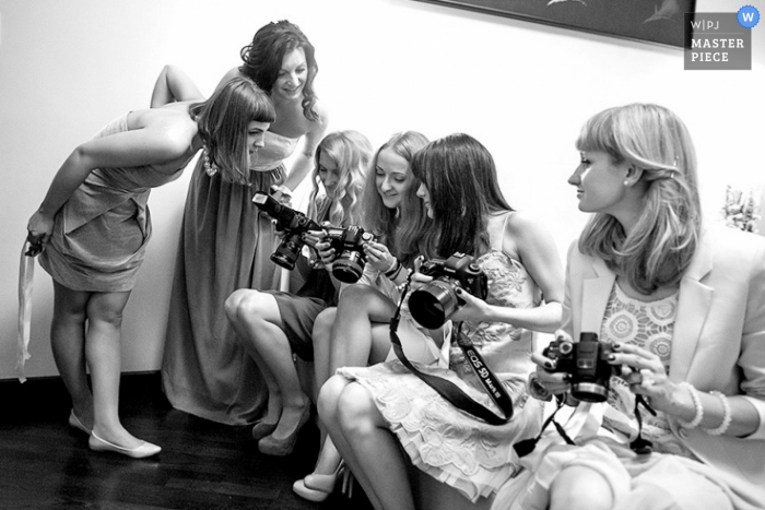 Bronx wedding photographer captured this black and white photo of a team of photographers comparing shots after the ceremony