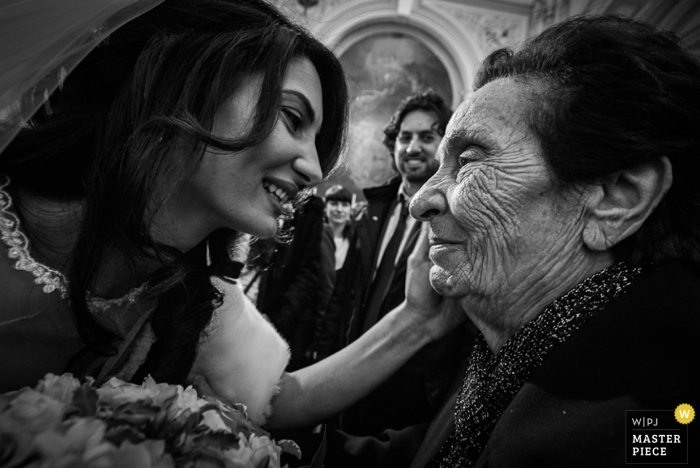 Messina wedding photographer captured this black and white photo of the bride sharing a tender moment with her grandmother after the Sicily ceremony