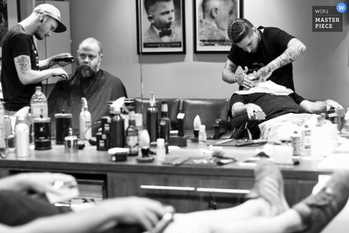 Melbourne wedding photographer captured this black and white photo of the groomsmen getting ready at the barber shop before the ceremony