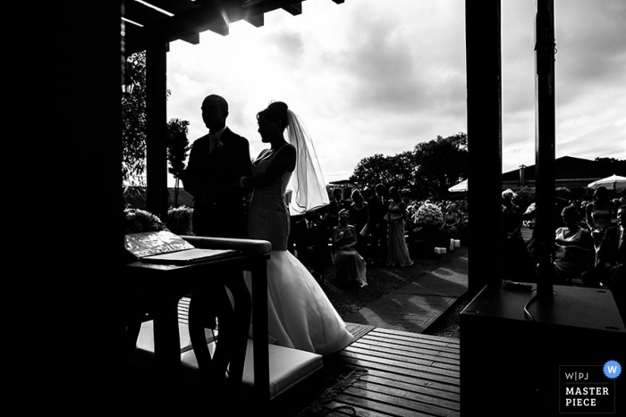Paraná wedding photographer captured this black and white silhouette photo of the bride and groom standing under an awning during their outdoor ceremony in Brazil