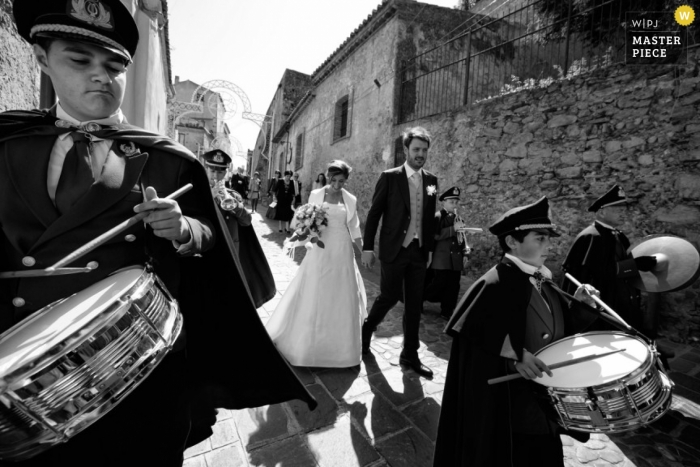 Reggio Calabria wedding photographer captured this photo of the bride and groom walking down the street with a marching band