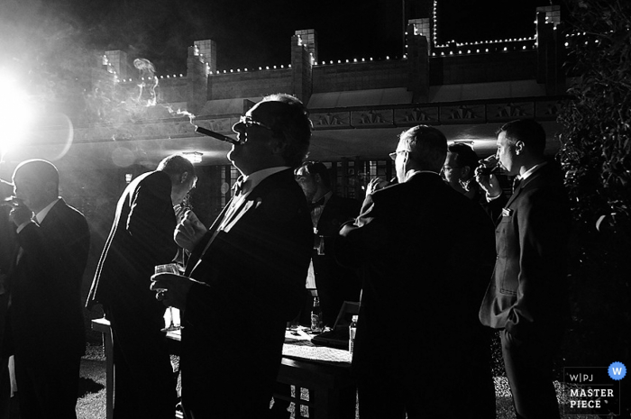Phoenix wedding photographer   black and white photo of the groomsmen enjoying cigars on the patio