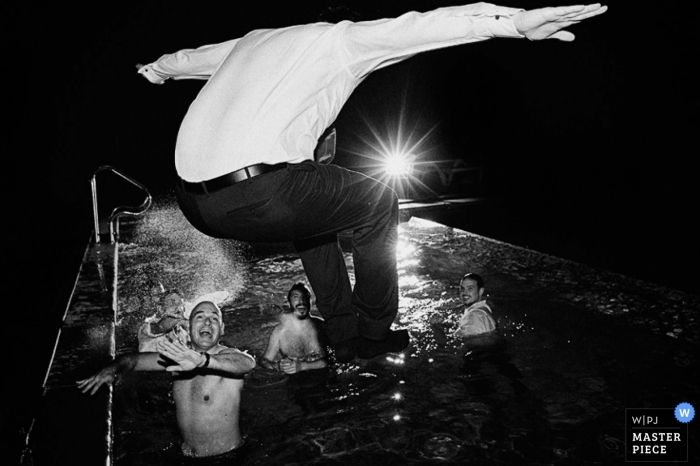 Buenos Aires wedding photographer captured this black and white photo of the groom jumping fully clothed into the pool
