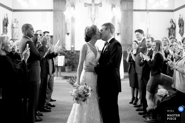 A wedding photographer captured this black and white photo of the newlyweds kissing at the ceremony as wedding guests cheer