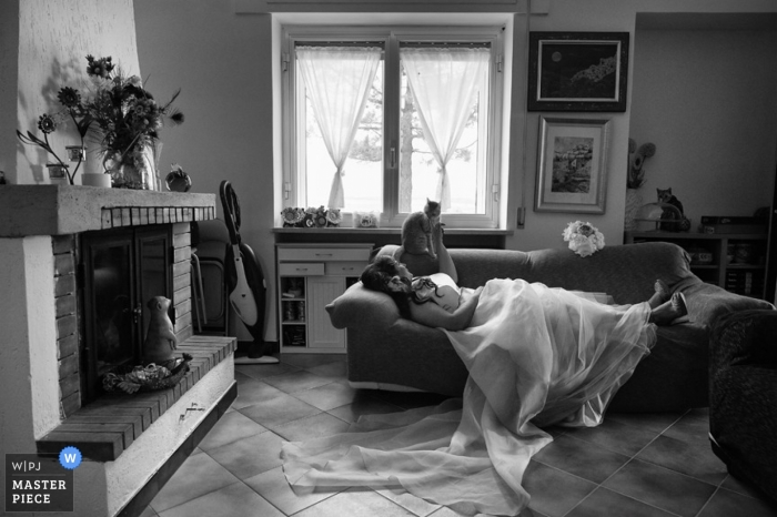 Italy Wedding Photography   Image contains: bride, cat, couch, sofa, home, rest, bouquet, fireplace