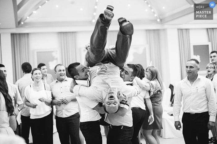 Photographie de mariage documentaire en Croatie | L'image contient: marié, à l'intérieur, réception, noir, blanc, invités de mariage, garçons d'honneur