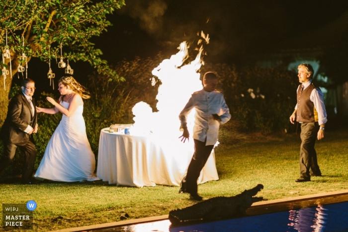 Photographie de mariage en Italie | L'image contient: plein air, couleur, flammes, piscine, nuit, couple, gâteau, feu, piscine, découpe