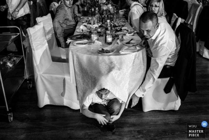 Fotografía de la boda de Varsovia   La imagen contiene: recepción, negro, blanco, mesa, niño, invitados a la boda