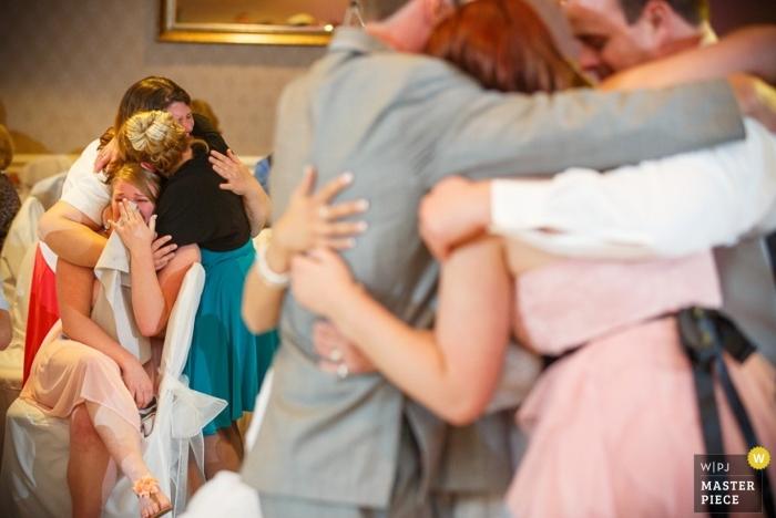 Photographie de mariage à Hartford | L'image contient: câlins, pleurs, intérieur, couleur, invités au mariage