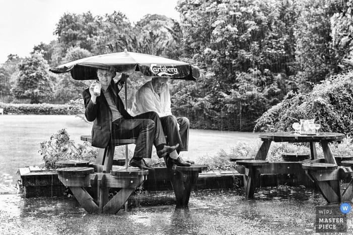 Dokumentarische Hochzeitsfotografie in Leicestershire | Bild enthält: Regen, Regenschirm, unten, gießen, getränkt