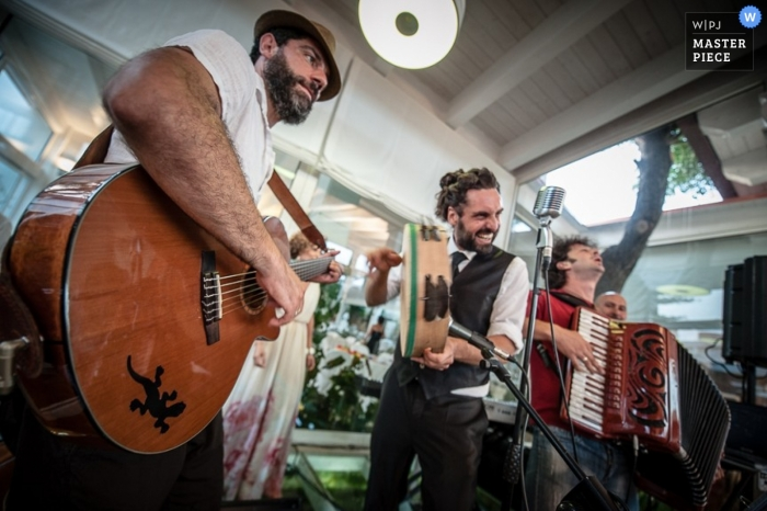 Wedding Photographer in Taranto | Image contains: reception, music, musicians, accordian, tambourine, guitar, band