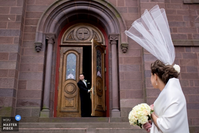 Massachusetts bride has veil flying away, upward outside of church.