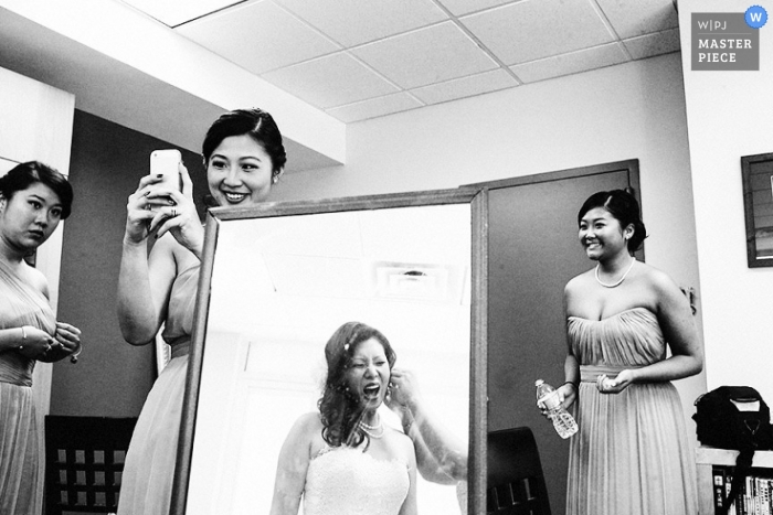 A black and white photo of a Bronx bride being assisted with the final jewelry for her wedding look reflected in a full length mirror surrounded and supported by her bridesmaids in NY
