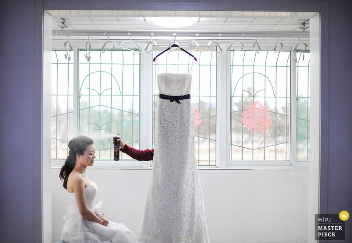 Hairspray in front of a window for a Shanxi bride as she prepares to dress in a deliberate photograph from China with severe lines softened by the dress hanging waiting for the bride