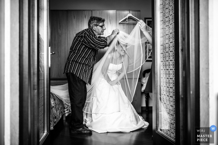 Last minute alterations to the bride's wedding veil and she bends to accommodate the seamstress in the doorway of her suite