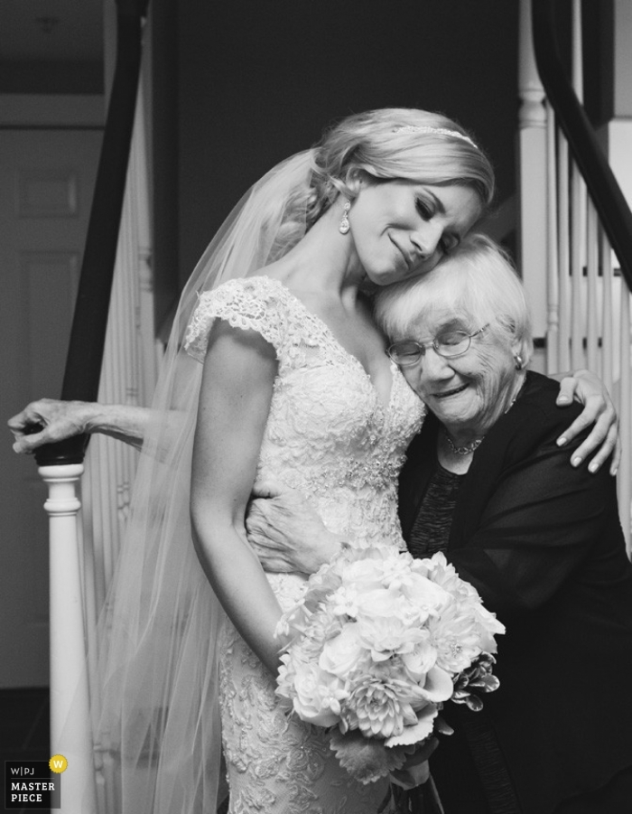A Porland bride and her grandmother share a special moment at the bottom of the stairs