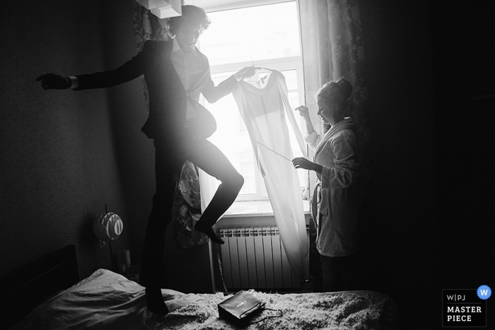 With a bounce on the bed a St Petersburg groom hands his bride her wedding dress while winter sunlight streams into a bedroom in Russia