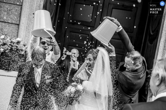 Lecco Wedding Fotojournalistiek | Afbeelding bevat: zwart en wit, bruid, bruidegom, het verlaten van de ceremonie, confetti, sluier, boeket, kerk, bruiloftsgasten